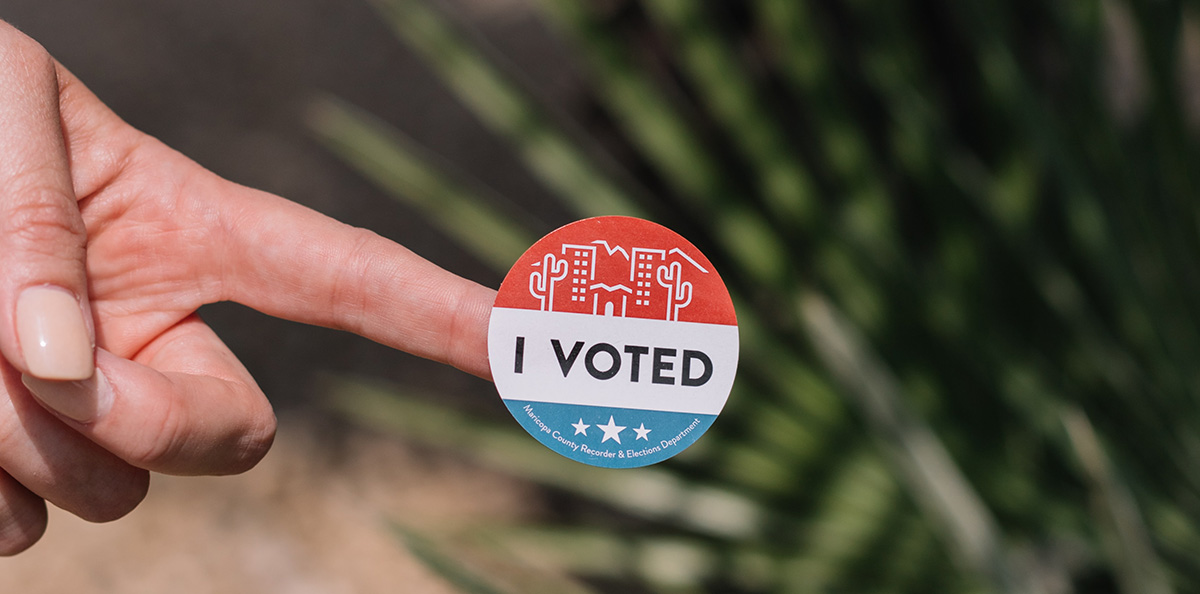 "Person showing off their ""I Voted"" sticker after votingckground"