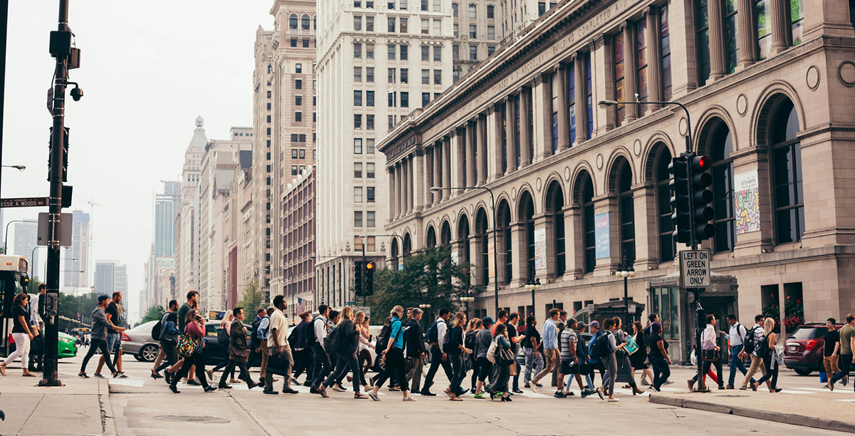 A large group of pedestrians crossing Michigan Avenue with the Chicago Cultural Center in the background.