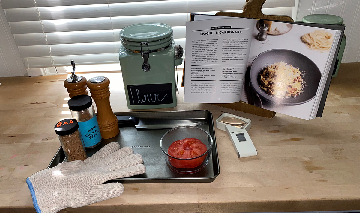 Kitchen tools organized before starting cooking include a tray, magnifier, oven glove, seasonings and the recipe.