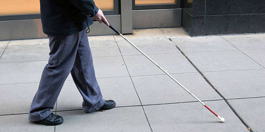 Man walking with a white cane.