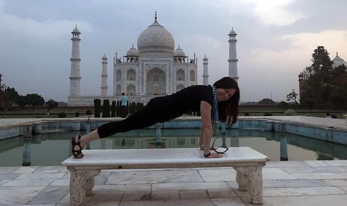Aly does the plank pose on a bench looking across the pond to the Taj Majal on her travels to India